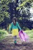 走沿森林地道路的女孩 库存照片