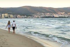 走沿沙子海滩的一个对在日落黑海Bulgari 库存图片
