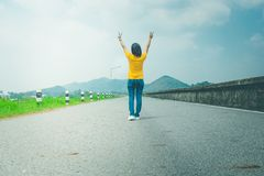 走沿沿边的乡下路的单独妇女旅客或背包徒步旅行者与水库,她举手在头顶上 库存图片