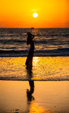 走沿海岛海岸线的一个孤独的女孩和有在湿沙子的反射 库存照片