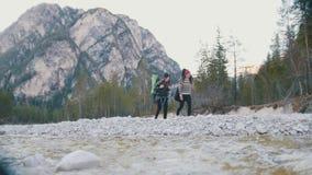 走沿海有背包和吉他的岩石河的两年轻女人在森林的背景和 股票录像