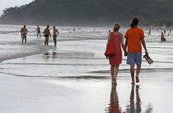 走沿海滩的夫妇在日落 免版税库存照片