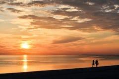 走沿海滨的夫妇在日落 图库摄影