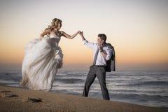 走沿海滩的年轻英俊的新娘夫妇在日出 免版税库存图片