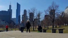走沿湖边平地的步行者在芝加哥,有湖岸驱动的在他们后 影视素材