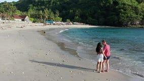 走沿热带海滩的男人和妇女在日落,跟踪年轻夫妇空中射击在度假获得的在的乐趣 股票视频
