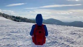 走沿用雪盖的山的上面的孤独的旅游女孩 清楚的冷淡的天气 股票视频