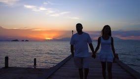 走沿码头的浪漫夫妇在日落 股票视频