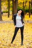 走沿秋天公园的一个美丽的女孩的画象 免版税库存照片