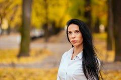 走沿秋天公园的一个美丽的女孩的画象 库存照片