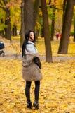 走沿秋天公园的一个美丽的女孩的画象 免版税库存图片