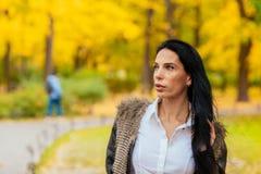 走沿秋天公园的一个美丽的女孩的画象 免版税图库摄影
