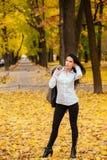 走沿秋天公园的一个美丽的女孩的画象 库存图片