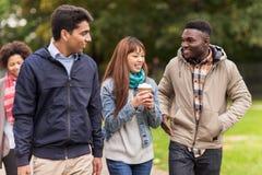 走沿秋天公园的愉快的朋友 免版税库存照片