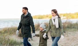 走沿秋天海滩的幸福家庭 免版税库存照片