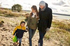 走沿秋天海滩的愉快的家庭 图库摄影