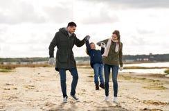 走沿秋天海滩的愉快的家庭 免版税库存图片