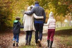 走沿秋天道路的家庭背面图 免版税图库摄影