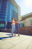 走沿街道和chattin的两位年轻美丽的女性 免版税库存照片