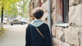 走沿街道的美丽的亭亭玉立的女孩慢动作画象然后转动,看照相机和微笑 年轻 股票录像