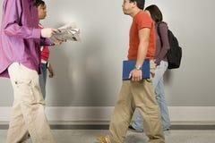 走沿走廊的四名学生 免版税库存图片