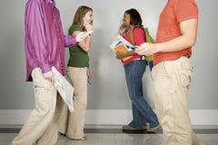 走沿走廊的四名学生 免版税库存照片