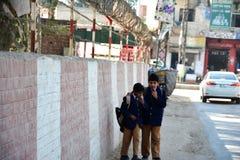 走沿边界墙和篱芭的两个巴基斯坦学校孩子 免版税库存照片