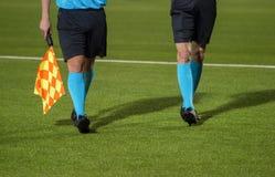 走沿边线的辅助裁判员在足球席子期间 免版税库存图片