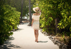 走沿道路的女孩在棕榈树之间 空白礼服 热带 马尔代夫 免版税库存图片