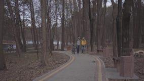 走沿道路的游人年轻夫妇在有背包的公园在他们的后面 人带领自行车和 影视素材