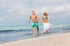走海滩日落假日的年轻愉快的夫妇 免版税库存图片