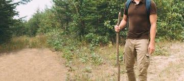 走用在小径的一根木棍子的远足者人 免版税图库摄影