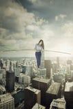 走用在绳索的一根棍子的女实业家 免版税库存照片