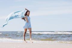 走由有一条蓝色挥动的围巾的海的俏丽的女孩 免版税库存图片