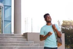 走由有袋子和巧妙的电话的台阶的男性大学生 免版税库存照片