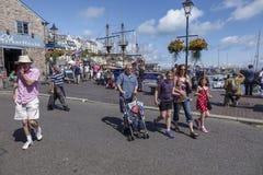 走由港口的假日游客怀有Brixham Torbay德文郡 免版税库存照片
