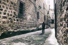 走由狭窄的中世纪街道的访客在普拉森西亚,西班牙 免版税库存图片