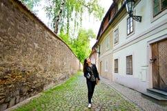 走由狭窄的街道的少妇在老镇 免版税库存照片
