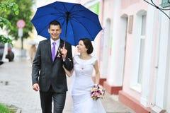 走由雨的年轻愉快的婚礼夫妇在一个老镇 库存图片