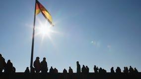 走的人们,休息在纽伦堡,德国旗子飞行反对天空蔚蓝 股票录像