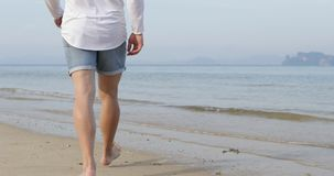 走的人浇灌在海滩,男性腿特写镜头后面背面图 股票录像