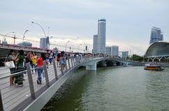走的人们参观在周年纪念桥梁的Merlion雕象 免版税库存照片