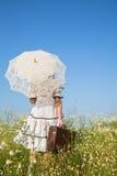 走的女孩在一个用花装饰的草甸 蓝天概念背景fo 免版税库存照片