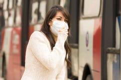 走的女孩戴着一个面具在城市 库存图片