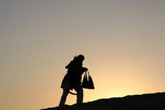 走的妇女上升现出轮廓反对黄昏微明 免版税库存照片