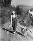 走的妇女她的在乡下公路的大牧羊犬(所有人被描述不更长生存,并且庄园不存在 供应商保单 免版税库存照片