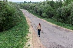 走的少妇的腿便衣的森林公路 旅游业寂寞,不确定性,选择的概念 库存照片
