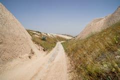走的未铺砌的粗砺的沙子足迹路线通过沙漠山放牧干古老红色谷风景与清楚的天空的 图库摄影
