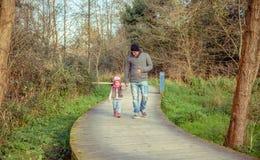 走的父亲和的女儿结合在一起使手 库存图片