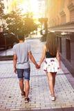 走穿过城市的年轻夫妇握手 免版税库存照片